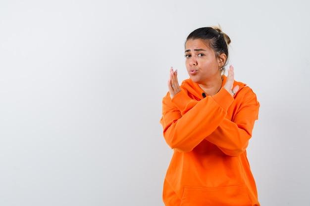 Femme en sweat à capuche orange montrant un geste d'arrêt et ayant l'air confiant