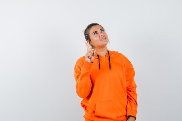 Femme en sweat à capuche orange pointant vers le haut et à la reconnaissance