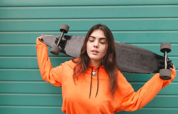 Femme en sweat à capuche se tient avec un longboard dans ses mains