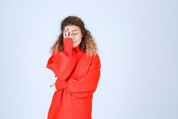 Femme en sweat-shirt rouge a l'air fatiguée et endormie.