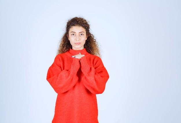 Femme en sweat-shirt rouge donnant des poses neutres.
