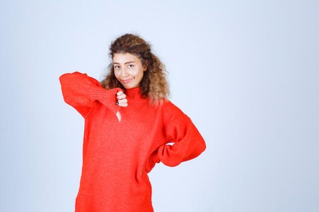 Femme en sweat-shirt rouge montrant le pouce vers le bas.