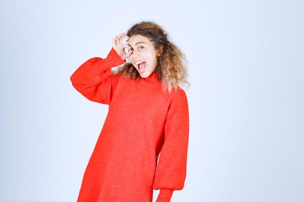 Femme en sweat-shirt rouge montrant un signe de plaisir.