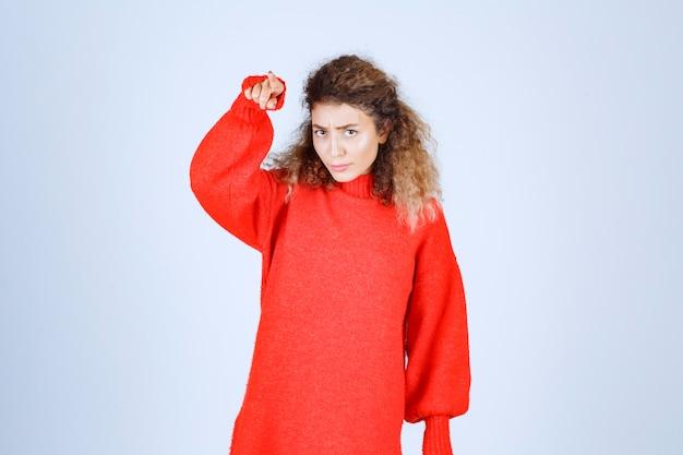 Femme en sweat-shirt rouge pointant quelqu'un vers l'avant.