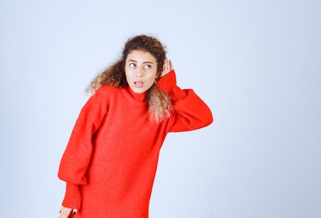Femme en sweat-shirt rouge pointant son oreille pour bien écouter.