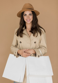 Femme sympathique en manteau et chapeau avec des filets à provisions à deux mains