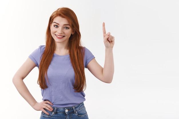 Une femme sympathique et mignonne offre de l'aide pour trouver exactement ce dont vous avez besoin, lever l'index, pointer vers le haut en souriant, partager l'endroit parfait pour la bannière, inviter à visiter la boutique en ligne, faire une recommandation, mur blanc