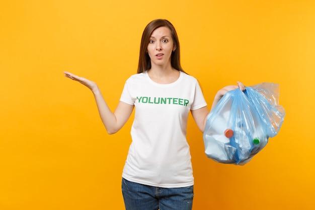 Femme en t-shirt bénévole, sac poubelle isolé sur fond jaune. aide d'assistance gratuite volontaire, grâce de charité. problème de pollution de l'environnement. arrêtez le concept de protection de l'environnement des ordures ménagères.