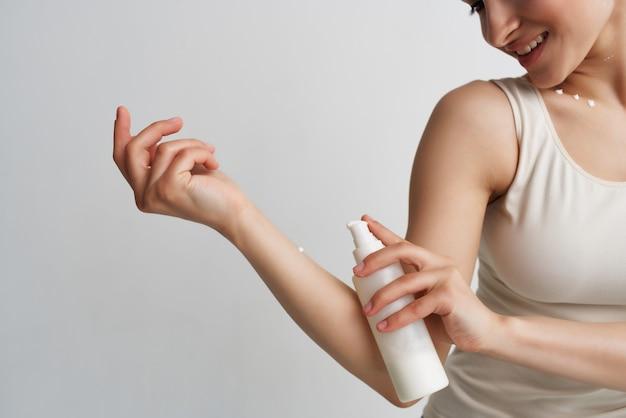 Une femme en t-shirt blanc applique une lotion sur une peau propre et hydratante à la main