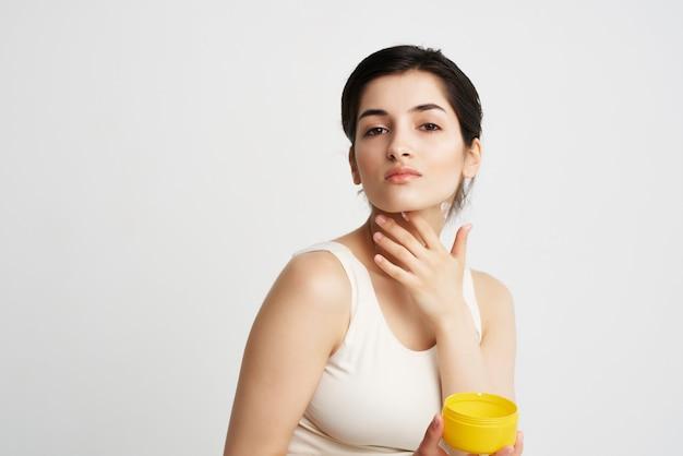 Femme en t-shirt blanc appliquer la crème sur la peau propre du corps