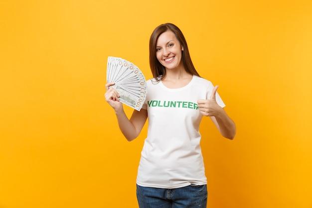 Une femme en t-shirt blanc avec inscription écrite en titre vert bénévole tient des billets de banque en dollars, de l'argent en espèces isolé sur fond jaune. aide d'assistance gratuite volontaire, concept de travail de grâce de charité.