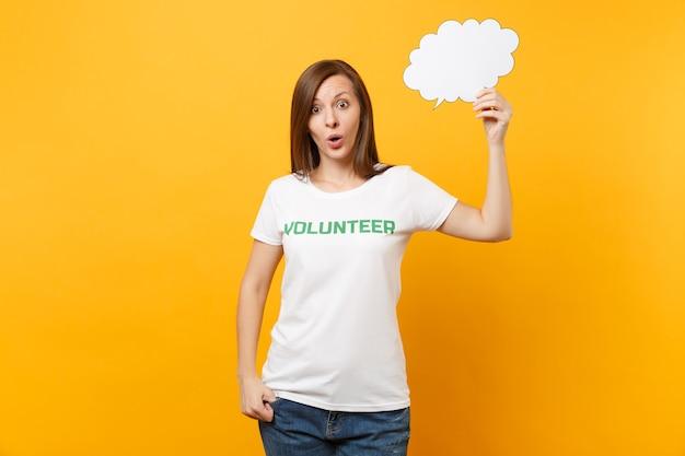 Femme en t-shirt blanc avec inscription écrite volontaire titre vert tenir vide vide dites bulle de dialogue nuage isolé sur fond jaune. l'aide volontaire gratuite aide le concept de travail de grâce de charité.