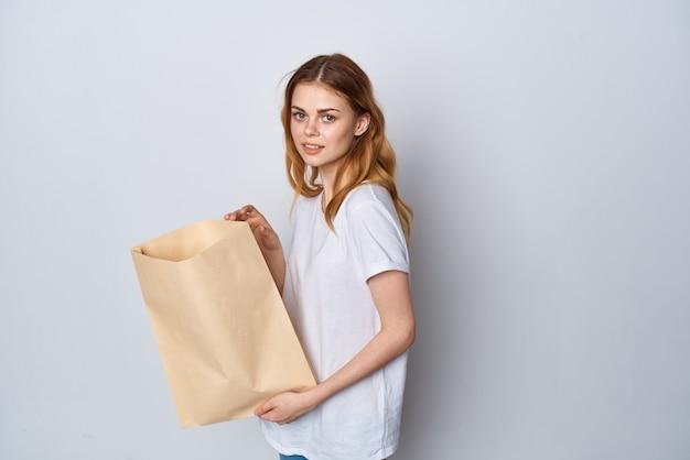 Femme en t-shirt blanc avec un paquet de courses d'emballage d'épicerie