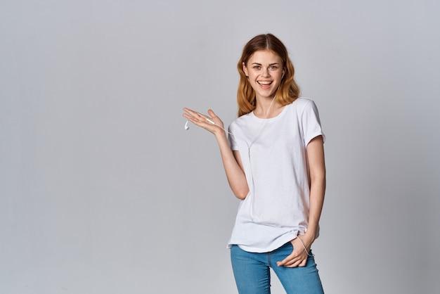 Femme en t-shirt blanc portant des écouteurs musique fun émotions mode de vie