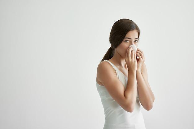 Femme en t-shirt blanc se mouche dans un foulard infection froid