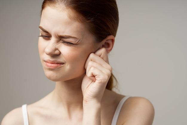 Femme en t-shirt blanc tenant des oreilles mécontentement des problèmes de santé de la migraine