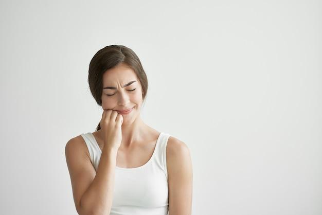 Femme en t-shirt blanc tenant sa tête maux de tête émotions mode de vie dépression. photo de haute qualité