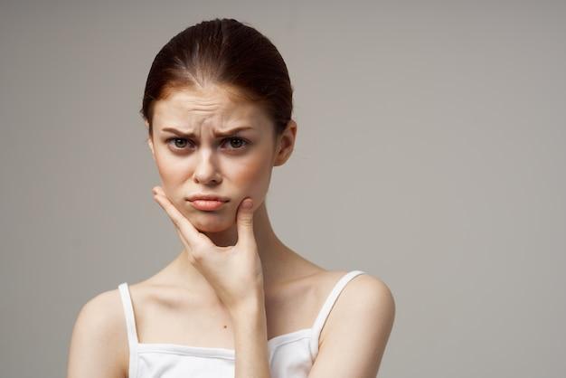 Femme en t-shirt blanc tient la main du modèle d'émotion de maux de dents propriétaire