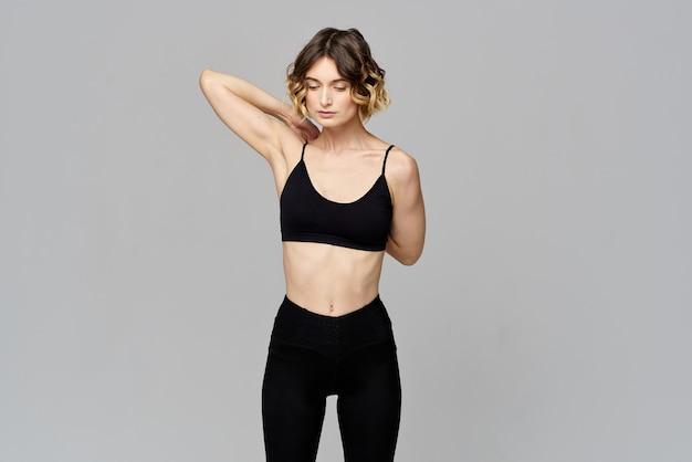 Femme en t-shirt court fait du sport sur un espace de copie d'exercice d'exercice gris.