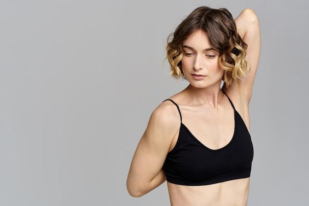 Femme en t-shirt court posant contre le mur