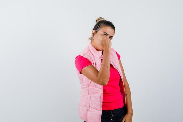 Femme en t-shirt, gilet montrant le poing fermé et à la rancune