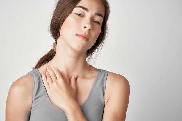 Femme en t-shirt gris douleurs au cou mécontentement problèmes de santé