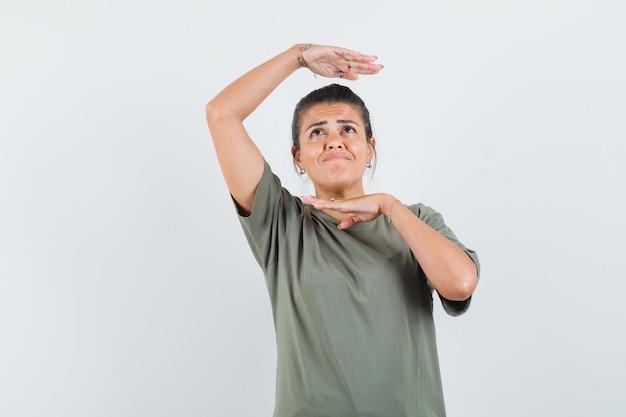 Femme en t-shirt montrant le geste de la danse traditionnelle et à la mignon