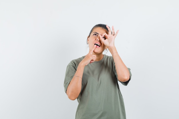 Femme en t-shirt montrant le signe ok sur les yeux et à la pensif