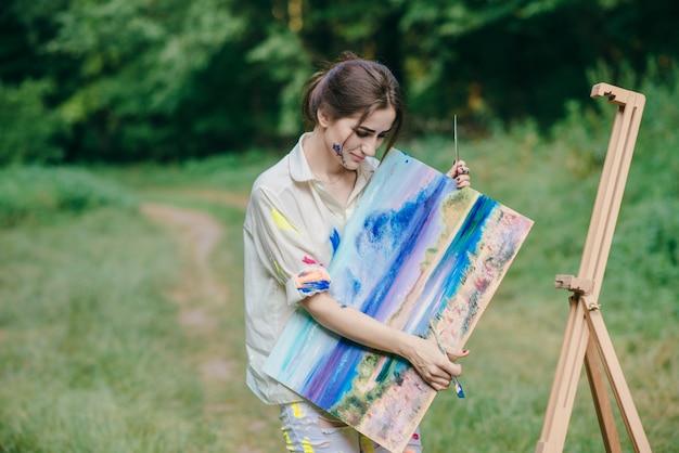 Femme avec t-shirt de peinture tachée regardant une image qui est dans sa main