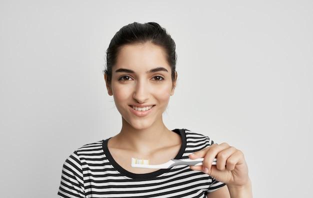 Femme en t-shirt rayé hygiène dentaire brosse à dents.