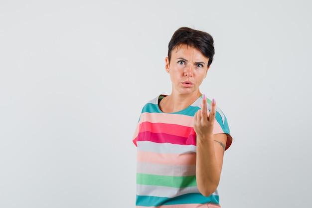 Femme en t-shirt rayé montrant deux doigts et à la confusion, vue de face.