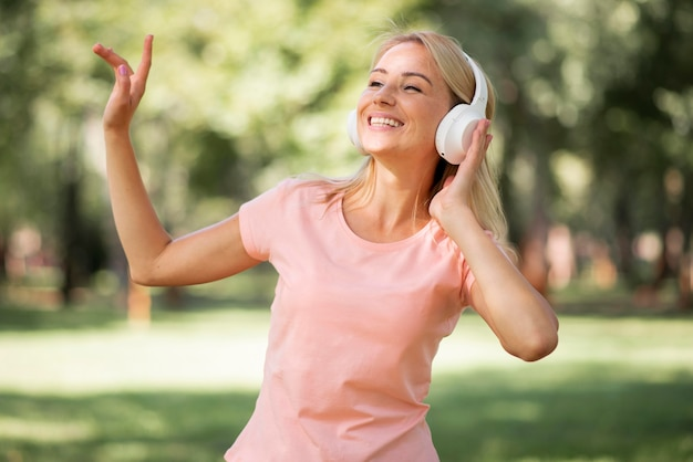 Femme en t-shirt rose, écouter de la musique