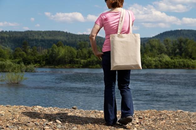 Femme en t-shirt rose portant une maquette de sac à provisions réutilisable vide.