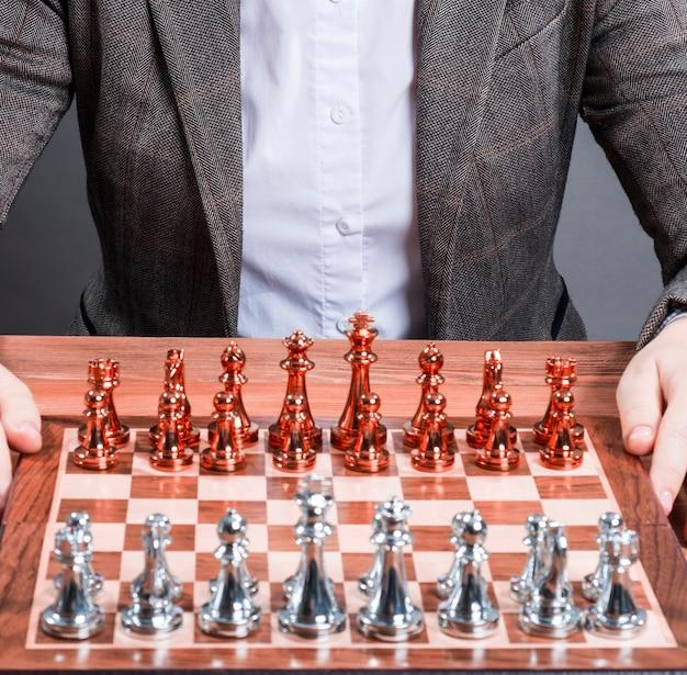 Une femme à une table avec un échiquier et des chiffres. concept de stratégie d'entreprise.