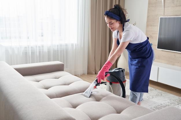Femme table de nettoyage avec aspirateur à la maison. concept de service de nettoyage
