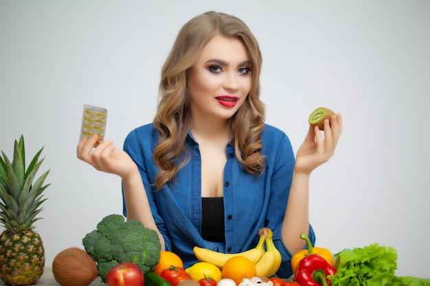 Femme à une table tenant un kiwi et des pilules sur un fond de fruits et légumes.