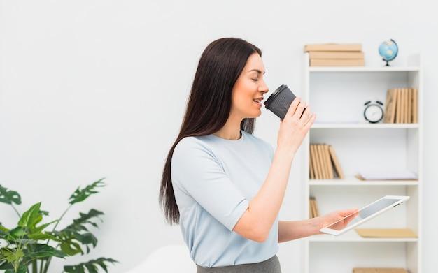 Femme avec tablette, boire du café au bureau