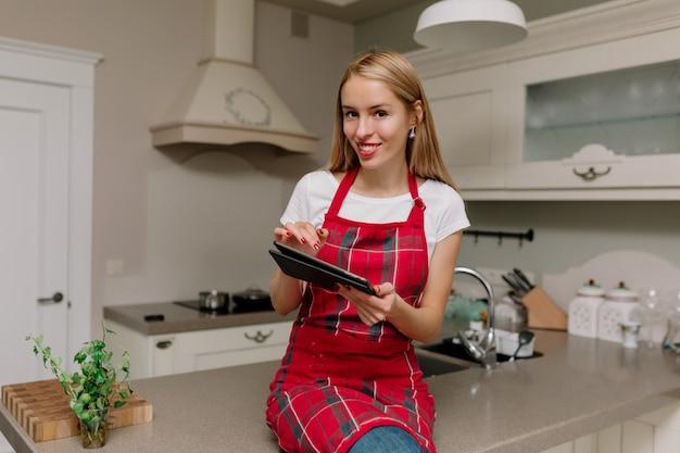 Femme avec tablette dans la cuisine