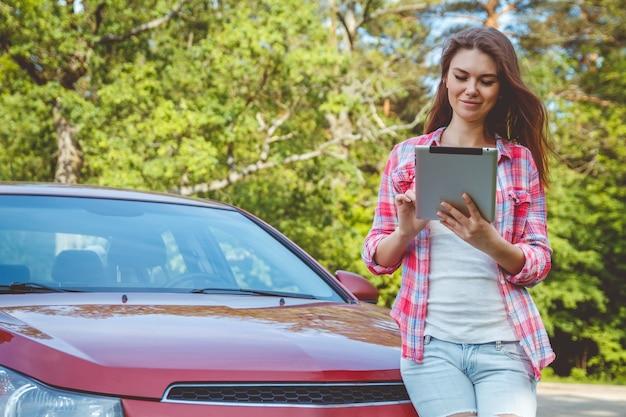 Femme avec une tablette dans les mains debout à côté de la voiture