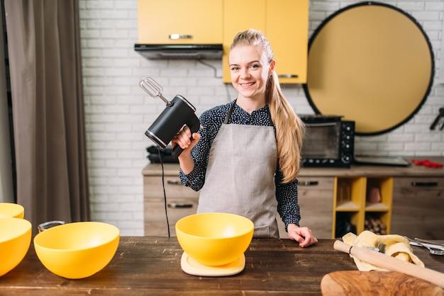 Femme en tablier ajoute du sucre dans un bol, fabrication de la pâte