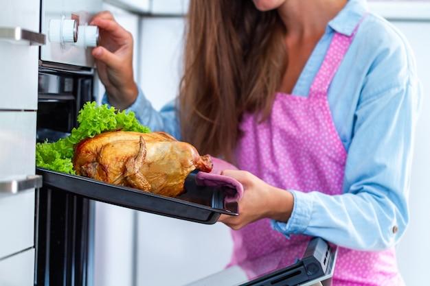 Femme, tablier, cuisson, poulet, legumes, four, dîner, maison canard au four pour les vacances