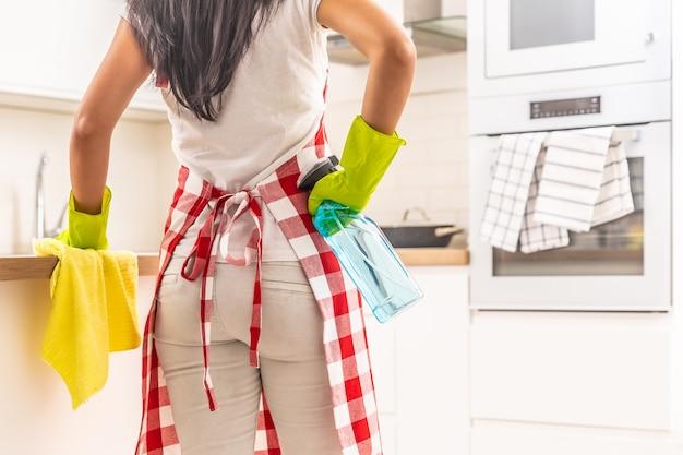 Femme avec un tablier et des gants en caoutchouc nettoyant la cuisine