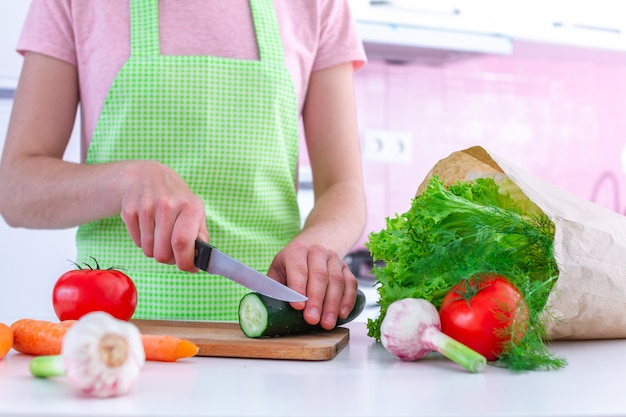 Femme en tablier hacher du concombre bio frais sur une planche à découper pour la cuisson des plats de légumes et des salades à la cuisine.