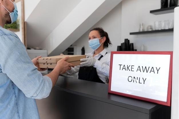 Femme avec tablier offrant des plats à emporter emballés à un client masculin
