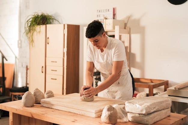 Femme en tablier à pétrir l'argile dans l'atelier