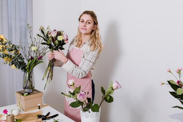 Femme en tablier, préparer des fleurs dans la boutique