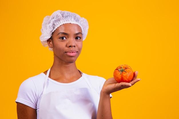 Femme en tablier tenant une tomate. recettes de tomates