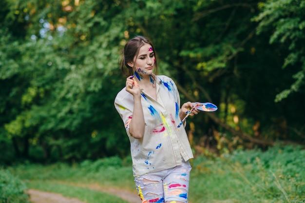 Femme taché par la peinture de marcher sur une forêt