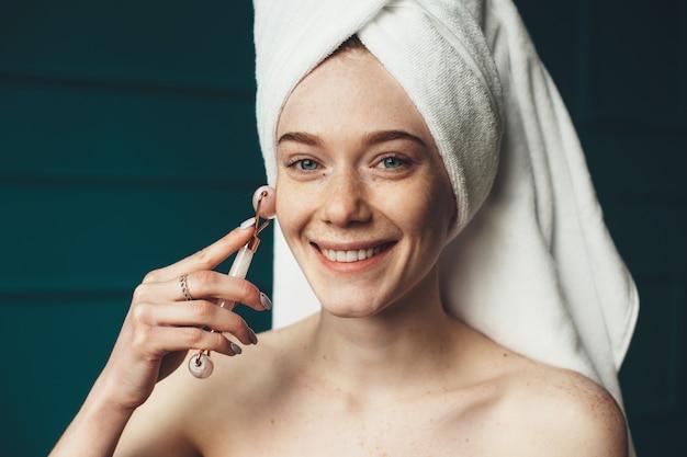 Femme avec des taches de rousseur souriant à la caméra tout en massant son visage avec un rouleau de derma