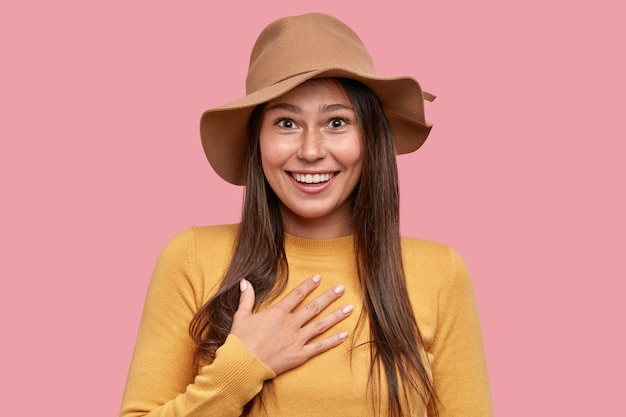 Femme de taches de rousseur surpris émotionnel avec expression positive garde la main sur la poitrine, sourit largement à la caméra